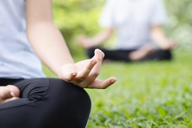 Yoga im park. schließen sie die hände einer frau, die meditiert