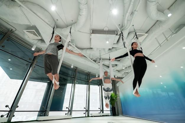 Yoga in der nähe des fensters. frauen und männer fühlen sich gut beim fliegenyoga in der nähe des fensters in einem geräumigen zimmer