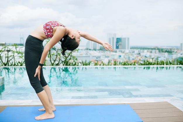 Yoga in der nähe des schwimmbades
