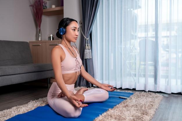 Yoga-konzept. ein süßes mädchen mit kopfhörern auf dem kopf sitzt und meditiert auf einem blauen karimath