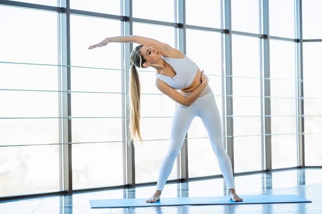 Yoga-mädchen, das drinnen sport treibt