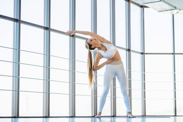 Yoga-mädchen, das sich vor den übungen aufwärmt