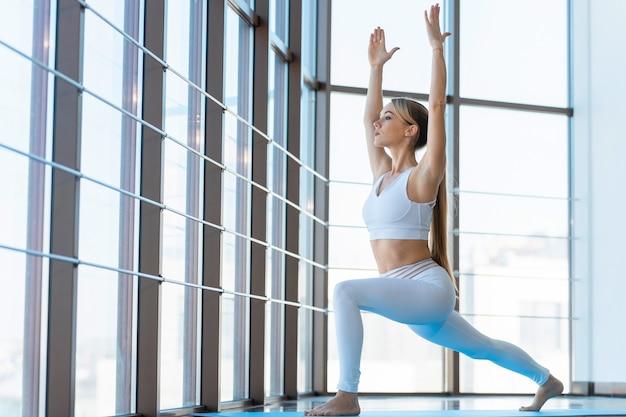 Yoga-mädchen in der kriegerpose innen