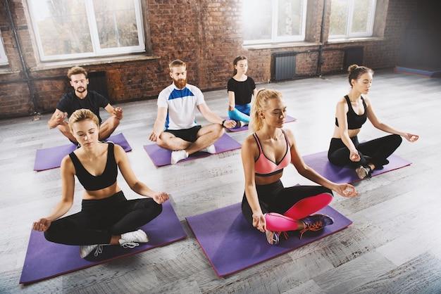 Yoga-meditation von jungen entspannten menschen im lotussitz im fitnesscenter