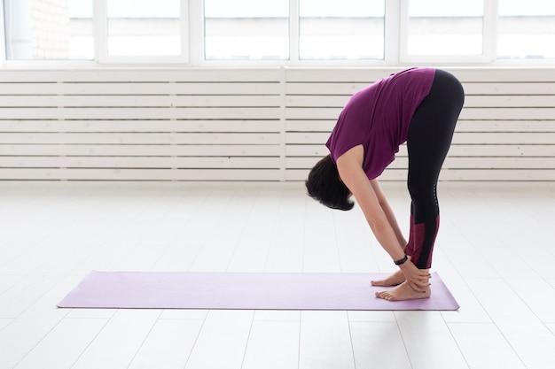 Yoga, menschenkonzept - eine frau mittleren alters, die im fitnessstudio yoga macht.