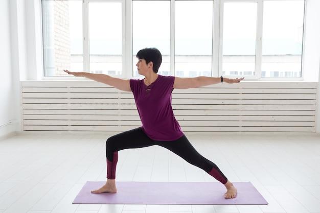 Yoga, menschenkonzept - eine frau mittleren alters, die yoga macht und versucht, eine asana zu machen