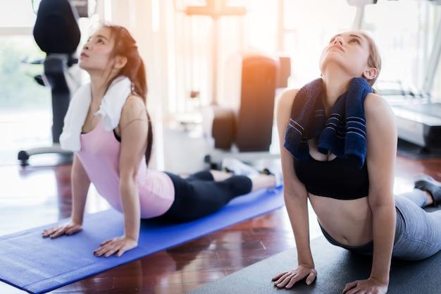 Yoga mit der frau, die körperhaltung auf sportmatte im fitness-club ausdehnt