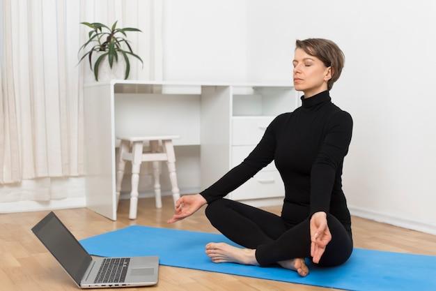 Yoga online auf einem laptop. eine frau meditiert zu hause.