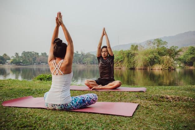 Yoga-partner sitzen mit den händen hoch