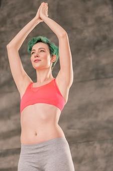 Yoga-pose machen. junge grünhaarige frau mit schönen bauchmuskeln, die sich beim yoga energetisiert fühlt