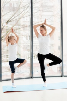 Yoga-pose mit mutter und smiley-tochter zu hause