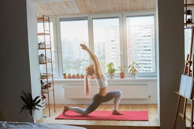 Yoga-praktizierende macht krieger-asanas, die zu hause auf dem balkon stehen