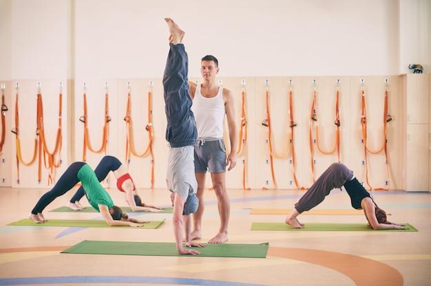 Yoga-praxis, ausbilder, der dem schüler hilft, im unterricht handstand zu machen, adho mukha vrikshasana, nach unten gerichtete baumpose, gruppe von menschen, die im sportclub trainieren, in voller länge