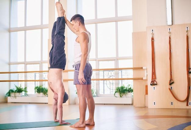 Yoga-praxis, lehrer, der dem schüler hilft, im unterricht handstand zu machen, adho mukha vrikshasana, nach unten gerichtete baumpose