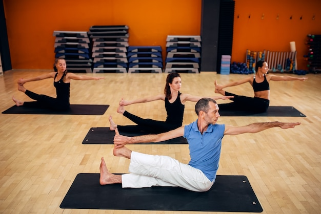 Yoga-trainingsklasse, weibliches gruppentraining mit männlichem trainer im fitnessstudio. yogi übung drinnen