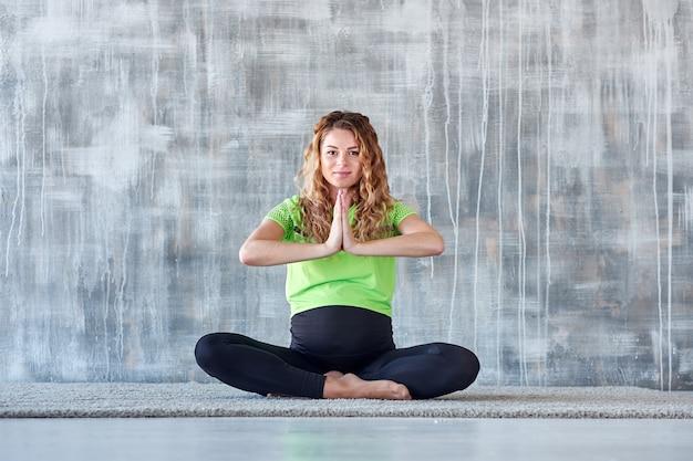 Yoga. übende yogameditation der schwangeren frau. gesundheitslebensstilkonzept und babypflege