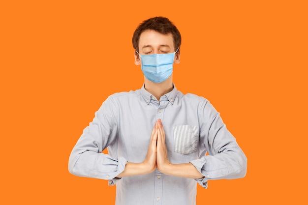 Yoga und meditation. porträt eines ruhigen jungen arbeitermannes mit chirurgischer medizinischer maske, der mit geschlossenen augen und meditierenden palmhänden steht. indoor-studioaufnahme auf orangem hintergrund isoliert.