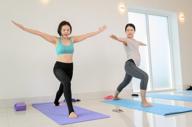 Yoga- und meditations-anfängerkurs mit personal trainer im fitnessbereich. training und bewegung für gesunde. asiatische frauenaktivität und lebensstil.