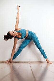 Yoga- und sportkonzept. eine junge kaukasische frau beschäftigt sich mit yoga und führt asana durch. weißer hintergrund im hintergrund. vertikal. platz kopieren.
