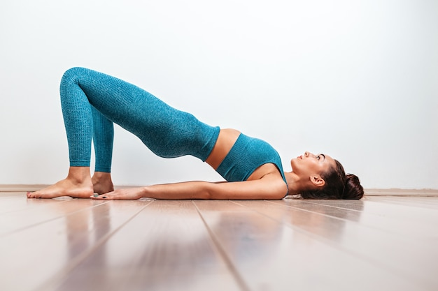 Yoga- und sportkonzept. eine junge kaukasische frau ist mit dem aufwärmen beschäftigt und führt die übungsbrücke durch. weißer hintergrund im hintergrund. kopieren.