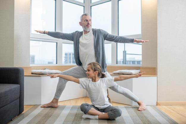 Yoga zu hause. papa und seine kinder machen zu hause zusammen yoga und sehen involviert aus