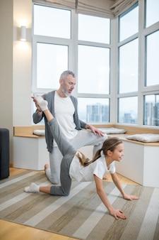 Yoga zu hause. papa und seine tochter machen zu hause zusammen yoga und sehen involviert aus