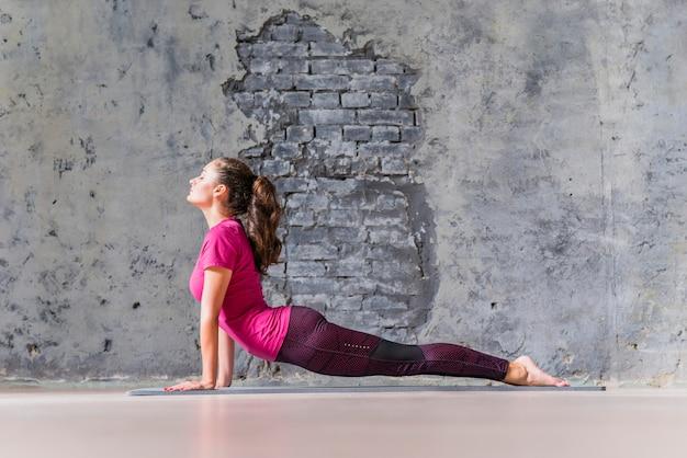 Yogaeignungsfrau, die übung gegen betonmauer ausdehnend übt