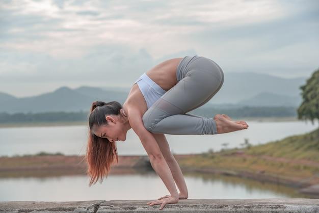 Yogafrau, die draußen yoga tut