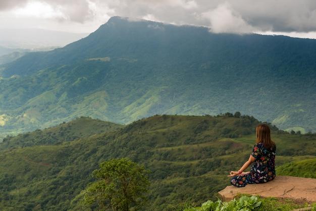 Yogafrau, die meditation auf dem felsen mit gebirgshintergrund tuend sitzt.