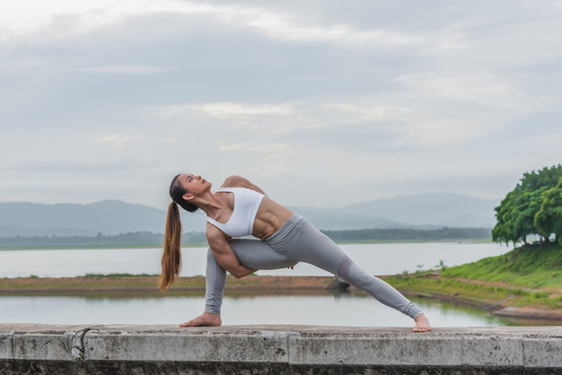 Yogafrau, die morgens übung in dem fluss tut.