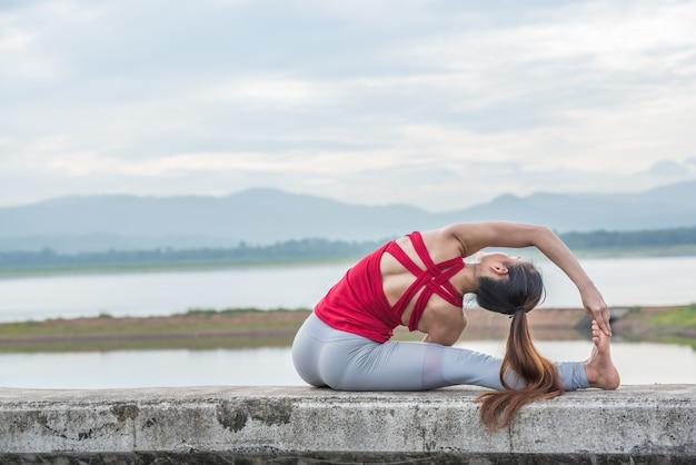 Yogafrau, die übung am see tut.
