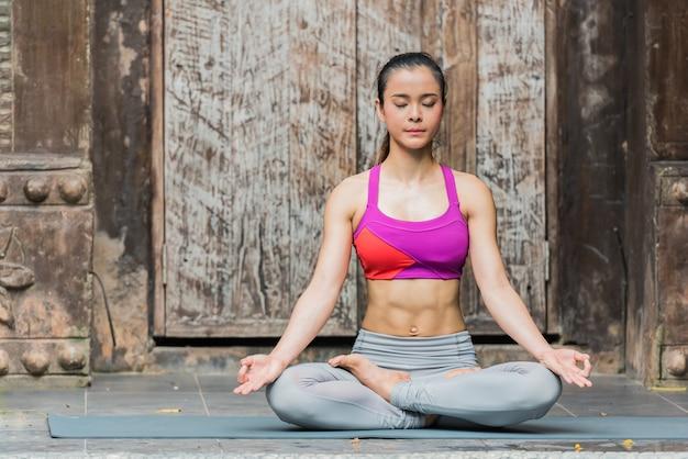 Yogafrau, die zu hause meditation mit lotoshaltung tut.