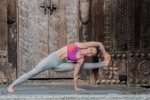 Yogafrau, die zu hause übung mit yogahaltung tut.