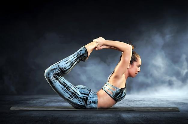 Yogafrau, welche die bogenhaltung demonstriert