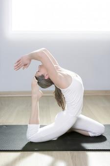 Yogafraueneignungsmädchen in der weißen meditation an der turnhalle