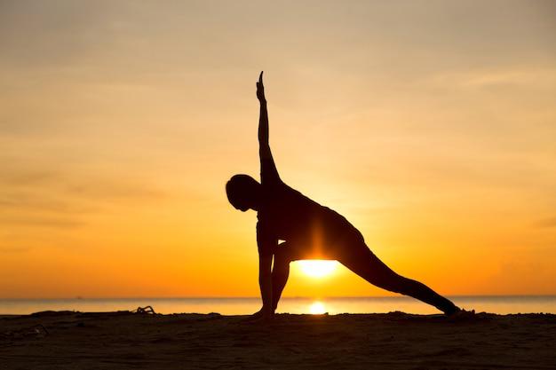 Yogafrauenschattenbild mit sonnenaufgang am morgen.
