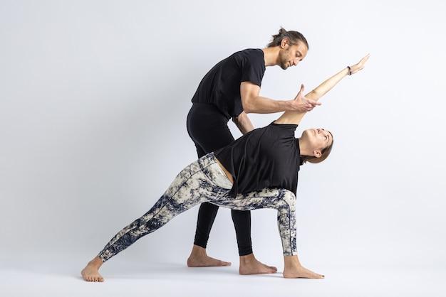 Yogalehrer korrigiert haltung zu seinem schüler isoliert auf weißem hintergrund