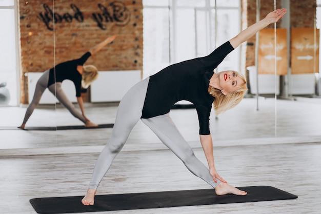 Yogalehrerin, die im fitnessstudio trainiert