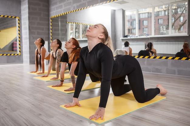 Yogalehrerin, die sich mit ihrer klasse im sportstudio ausdehnt