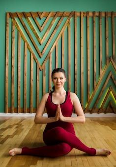 Yogalehrerin in einem burgunderfarbenen overall macht eine yoga-pose und schaut im fitnessstudio nach vorne
