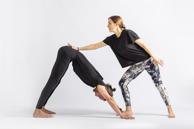 Yogalehrerin korrigiert die haltung ihres schülers isoliert auf weißem hintergrund