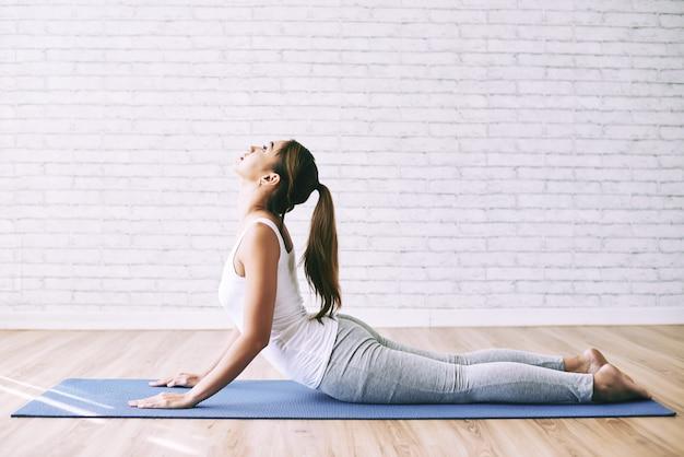 Yogamädchen, das zu hause kobra asana als ihre morgenübung tut