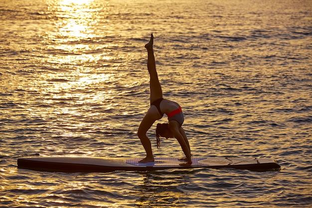 Yogamädchen über sup stehen surfbrett