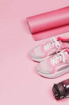 Yogamatte, sportschuhe, flasche wasser auf rosa