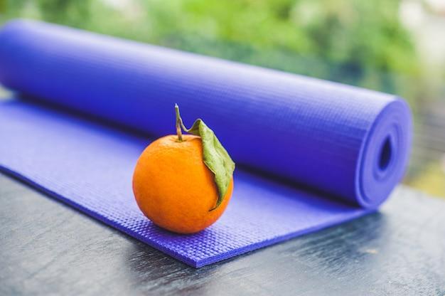 Yogamatte und orange auf einem hölzernen hintergrund