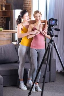 Yogastunde. nette positive junge frauen, die vor der kamera stehen und yoga praktizieren, während sie yoga-lektion aufzeichnen