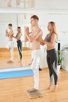 Yogatherapeut, der haltung des mannes einstellt, der auf nagelbett steht