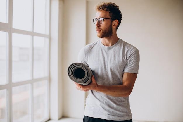 Yogatrainer mit matte am fenster stehend