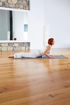 Yogaübung in der bretterbodenturnhalle und -spiegel