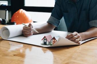 Yong-Architektenmann, der mit Plänen und Modell des kleinen Hauses arbeitet